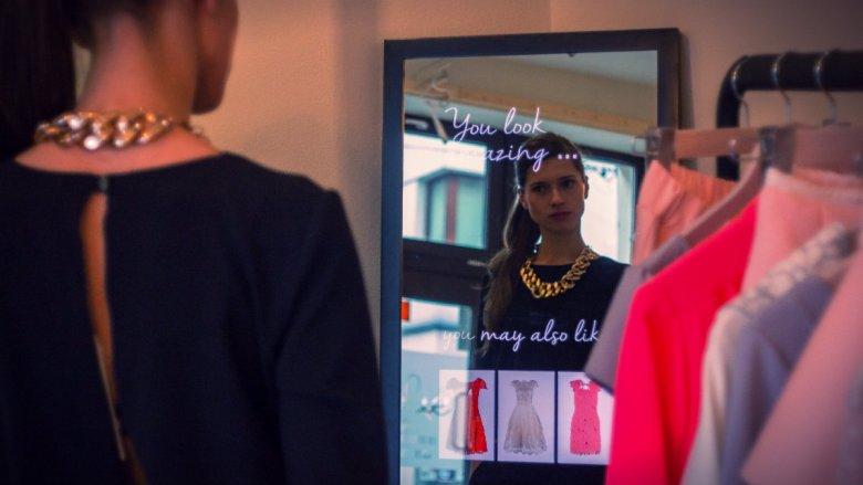 Kobieta, która przymierza sukienkę, zobaczy w lustrze Abyss Glass komplement.
