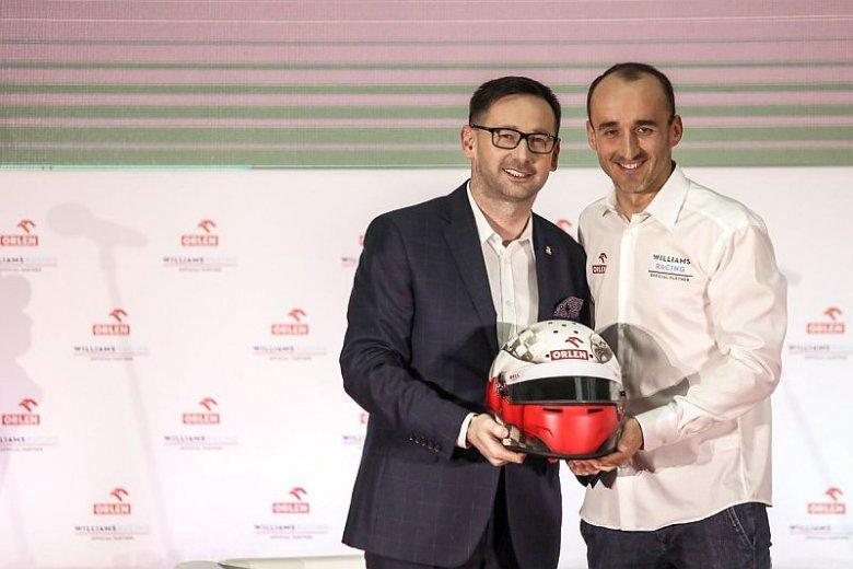 Prezes Orlenu Daniel Obajtek i Robert Kubica pokazują kask, w którym będzie się ścigał nasz rodak