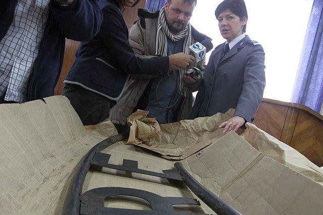 Lidia Puchacz pokazuje dziennikarzom odzyskany przez policję napis z byłego obozu koncentracyjnego w Oświęciumiu