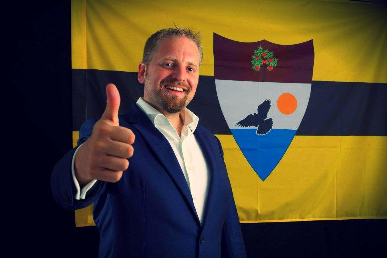 Vít Jedlička pozuje na tle flagi Liberlandu w sierpniu 2015, po tym jak pierwsi Liberlandczycy zasiedlili jego kraj