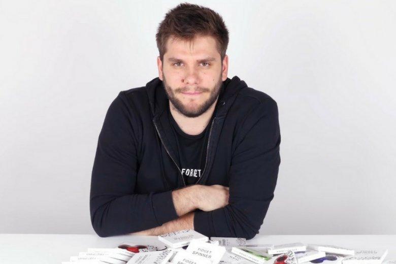 Adam, youtuber znany jako Poszukiwacz, rozpakowuje pudełko ze stosem fidget spinnerów.