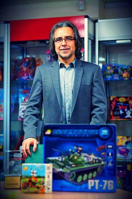 Prezes COBI, Robert Podleś, na tle wyprodukowanych zabawek