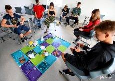Uczniowie na lekcji informatyki programują małe roboty Photony