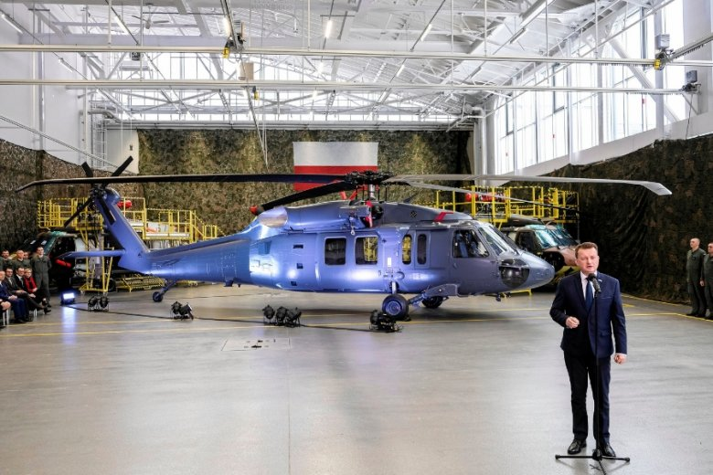 Minister obrony Mariusz Błaszczak na tle zakupionych śmigłowców Black Hawk S70i. Dopuścił się kilku nieprawdziwych stwierdzeń. To nie śmigłowiec gotowy do boju, a szkielet, wymagający dalszych modyfikacji. W dodatku nie powstaje w całości w Polsce - w Mie